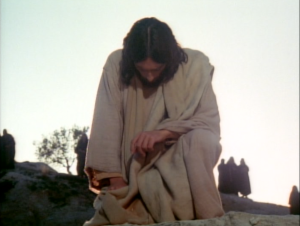Jesus, in the movie Jesus of Nazareth, is kneeling before the tomb of Lazarus